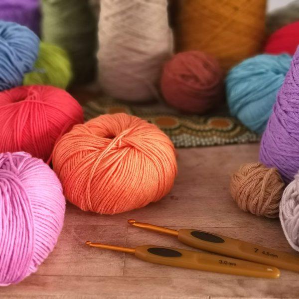 ovillos de distintos colores y texturas para tejer el clutch étnico de ganchillo Alocrazy